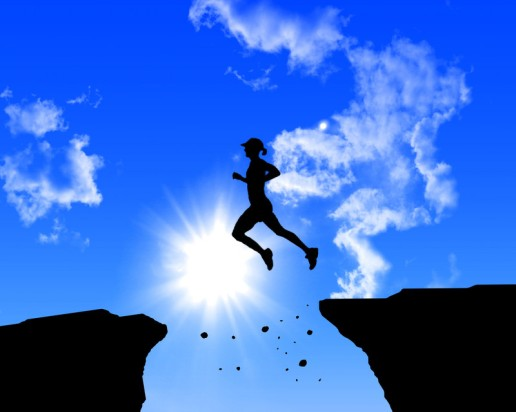 woman leaping across cliff (blue background)